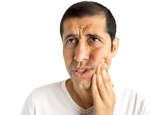 A middle-aged man looking up and holding his cheek due to an extruded tooth