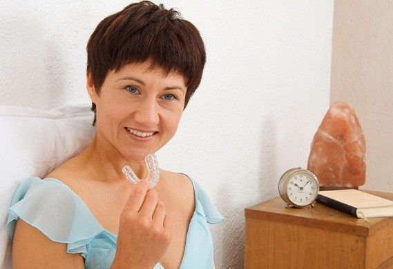 woman holding sleep apnea therapy device
