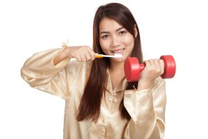 Asian woman in pajamas with toothbrush and red dumbbell