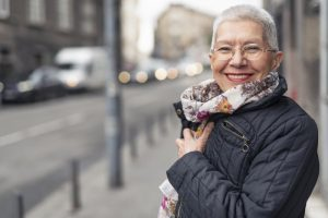an older woman smiling while wearing winter clothes