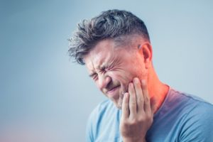 man with mouth pain who needs emergency dentist in Houston