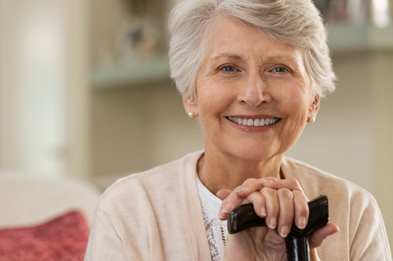 Older woman with a walker smiling on a couch