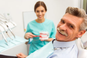 Elderly man sitting in dentist's chair, smiling